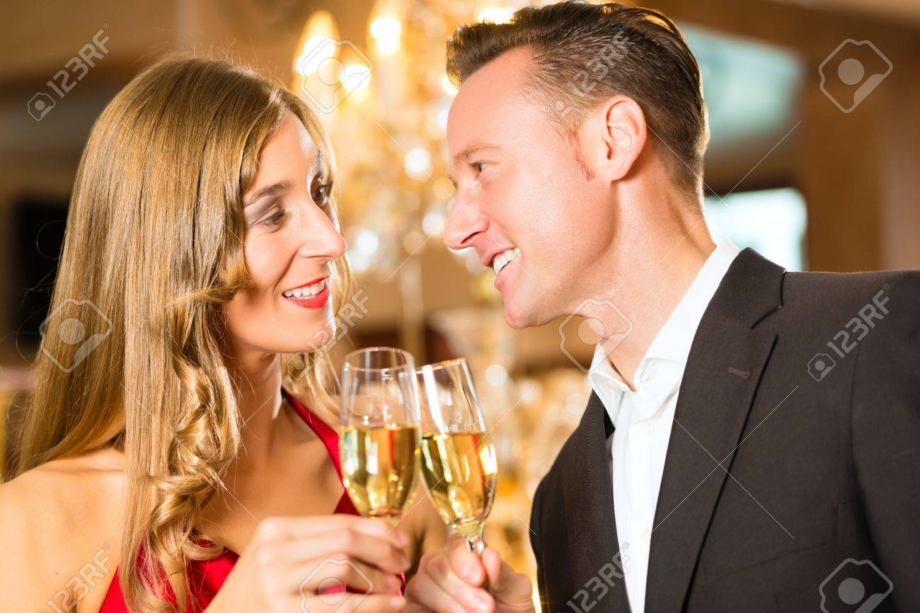Couple, man and woman, drinking champagne in a fine dining restaurant, each with glass of sparkling wine in hand Stock Photo - 19000776