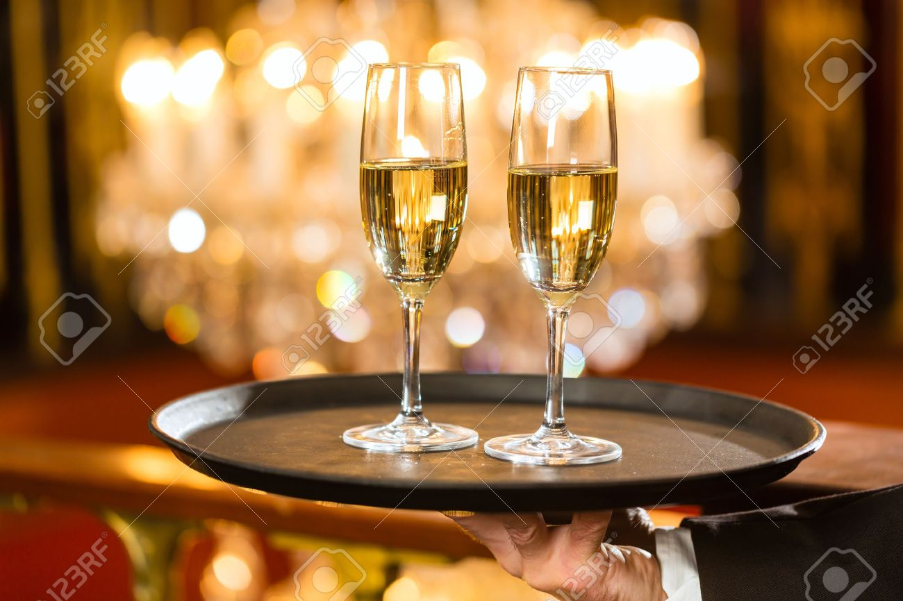 Waiter served champagne glasses on a tray in a fine dining restaurant, a large chandelier is in Background Stock Photo - 19000763