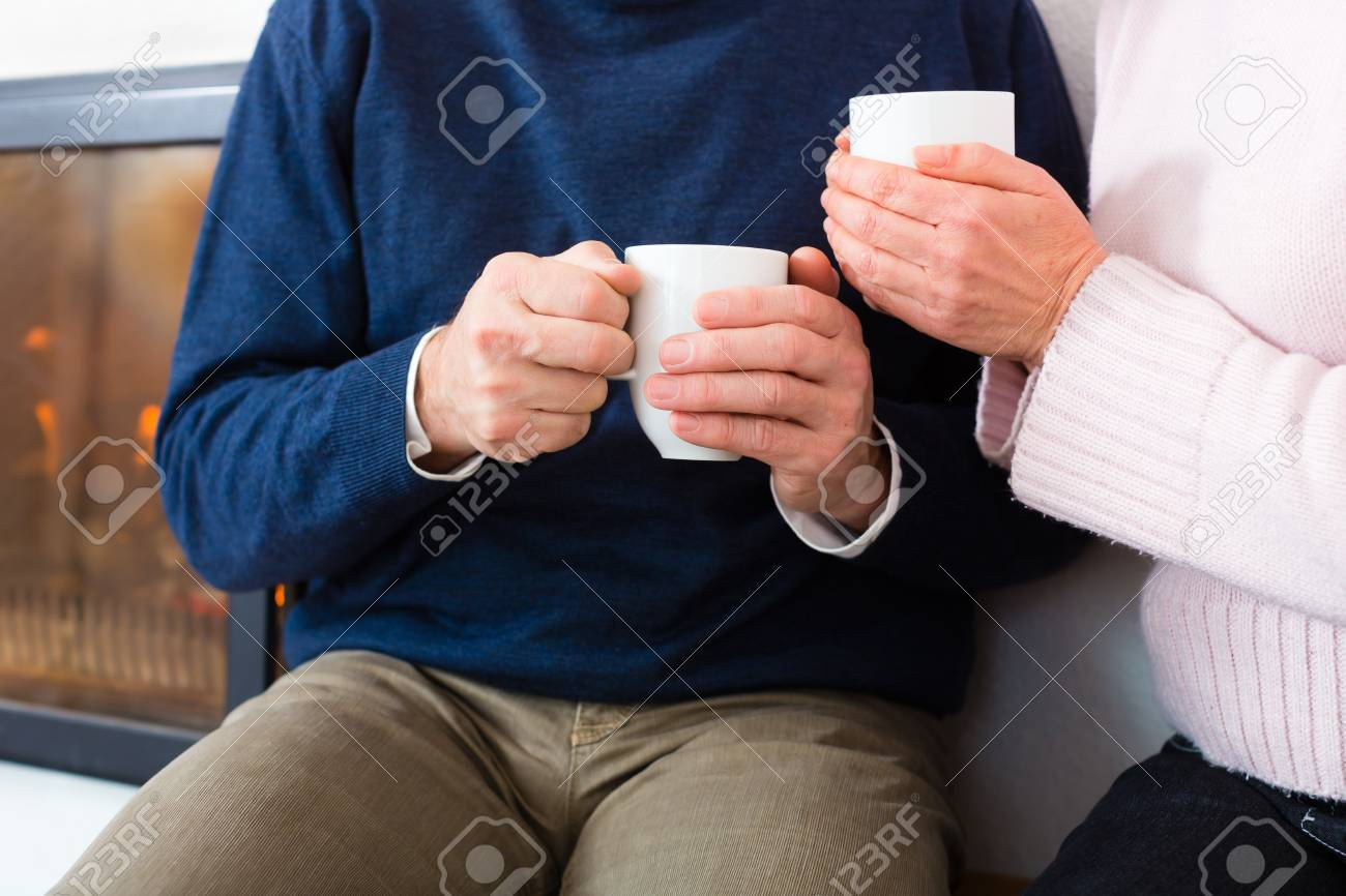 Seniors at home in front of fireplace with tea cup Stock Photo - 19226113