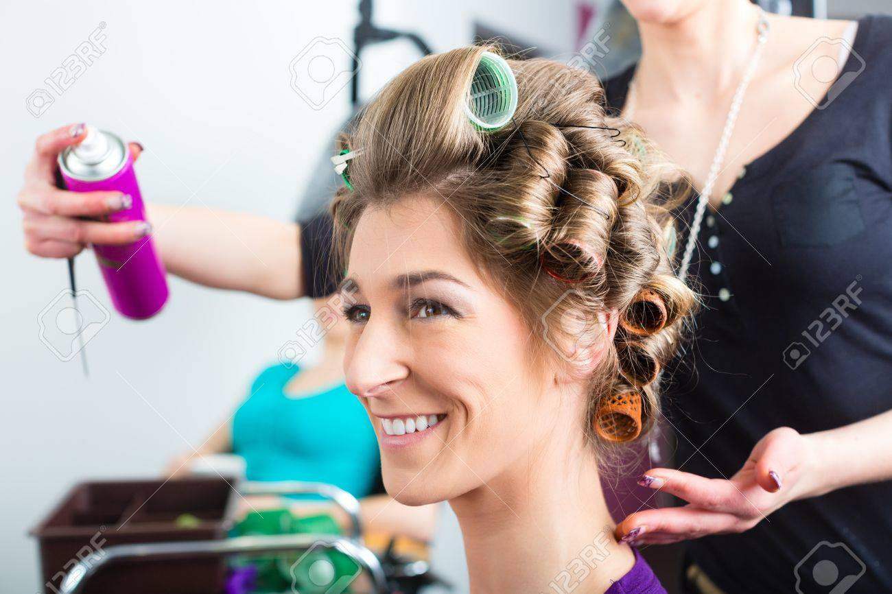 Hairdresser - hair stylist curling hairs, a female customer gets a haircut Stock Photo - 19762011