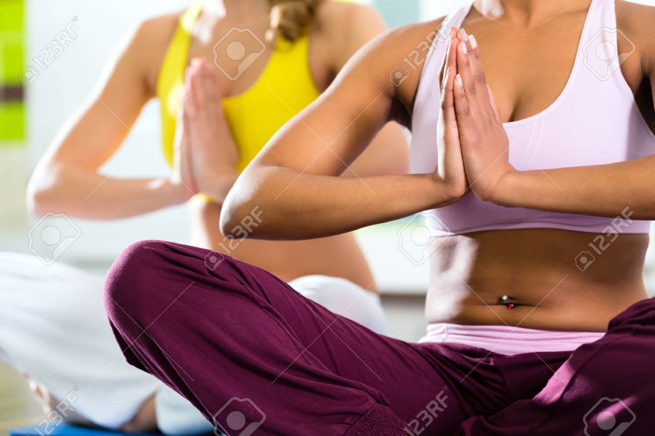 Young women doing yoga and meditation in gym for better fitness, caucasian and latina people Stock Photo - 19809521