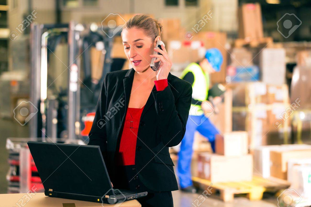 Friendly Woman, dispatcher or supervisor using cell phone and laptop at warehouse of forwarding company, smiling, a forklift is in Background Stock Photo - 19942163
