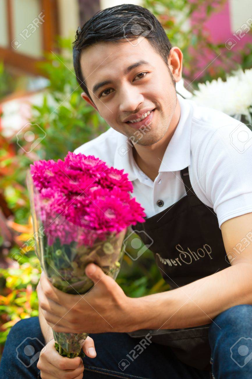 Friendly asian florist or seller in a flower shop holding a flower friendly asian florist or seller in a flower shop holding a flower bouquet stock photo izmirmasajfo