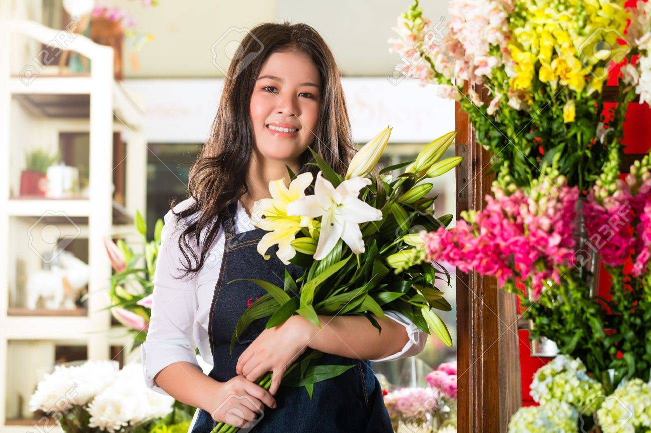 Friendly Asian florist or Saleswoman in a flower shop, holding a flower bouquet Stock Photo - 19942339