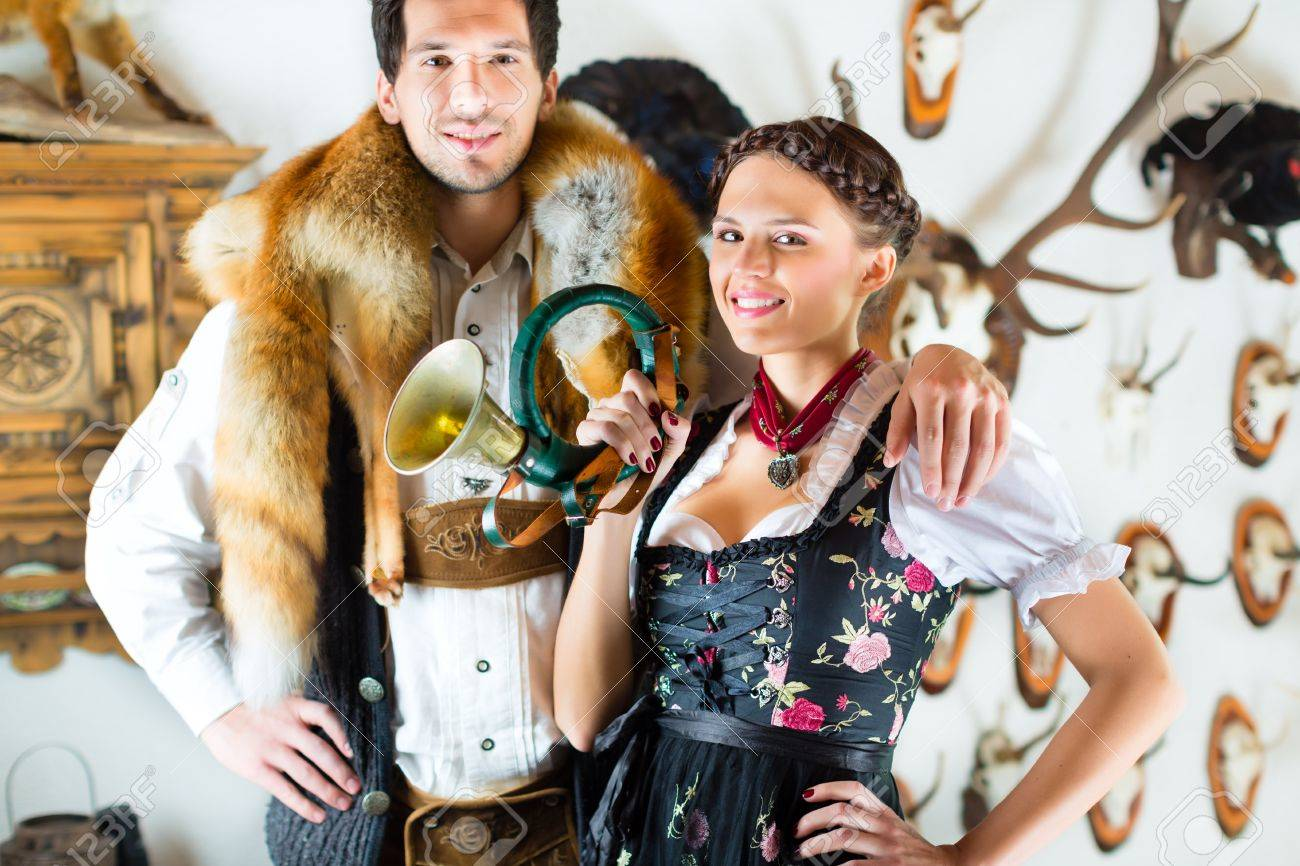 Young hunter with his wife and a bugle in front of a Wall with different horns, antlers and trophies in an alpine cabin Stock Photo - 20836810