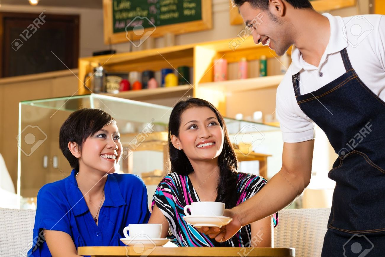 Asian female friends enjoying her leisure time in a cafe, drinking cappuccino and talking about some things, a Indonesian waiter serving the coffee - 20836835