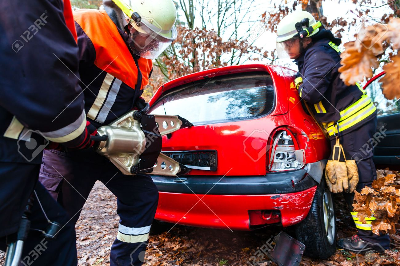 Accident - Fire brigade rescues accident Victim of a car using a hydraulic rescue tool Stock Photo - 21400882