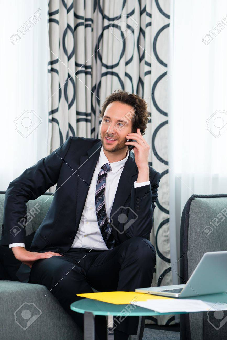 Businessman working in business hotel, he discusses some documents with a customer on the phone Stock Photo - 22046749