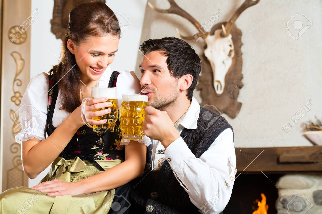 Couple in a traditional mountain hut with fireplace drinking beer Stock Photo - 22041729