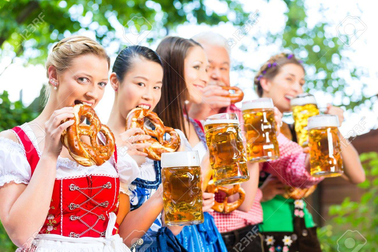 In Beer garden - friends, man and women in Tracht, Dirndl and Lederhosen drinking a fresh beer in Bavaria, Germany Stock Photo - 22088045
