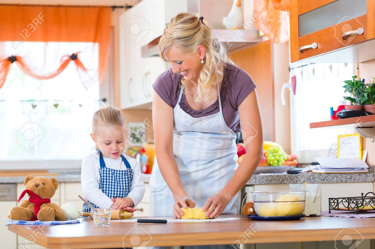 Family home baking - Mother and daughter baking cookies together at home Stock Photo - 22401255