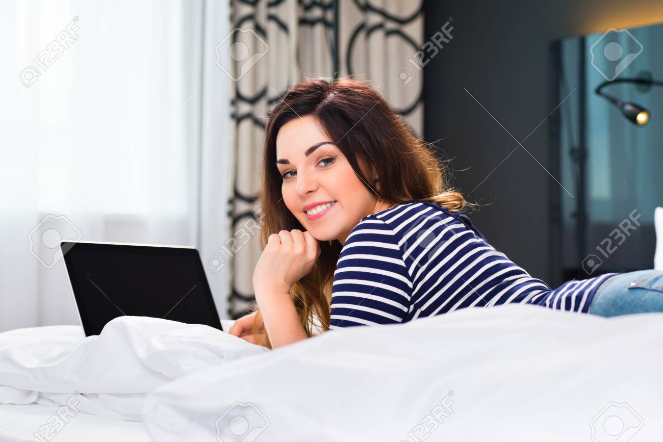 Young woman lying in the bed of a hotel room, she are on vacation and using the wifi in the room for internet with the computer Stock Photo - 22401273