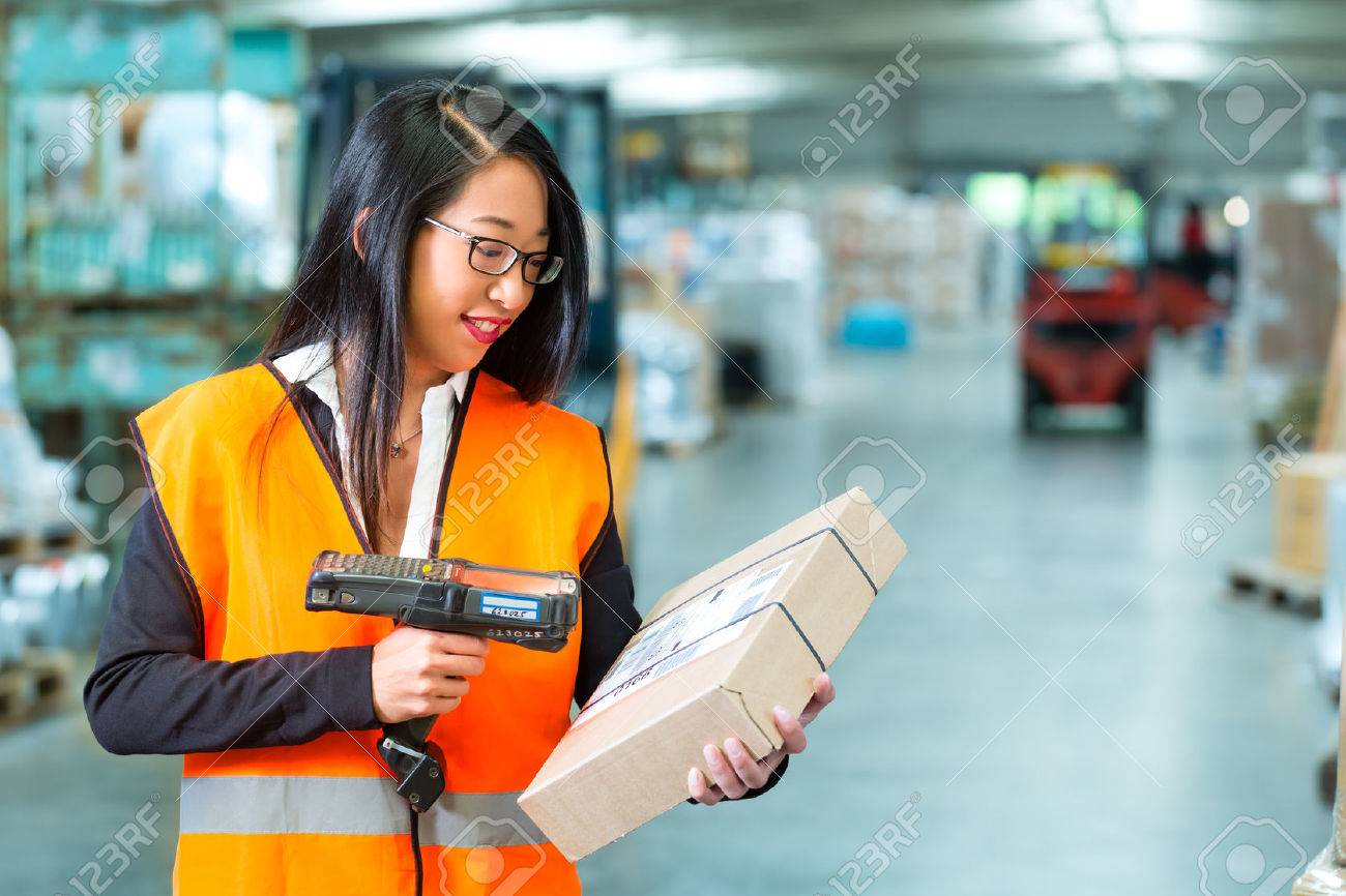 Logistics - female worker or shipper with protective vest and scanner, scans bar-code of package, he standing at warehouse of freight forwarding company Stock Photo - 22400472