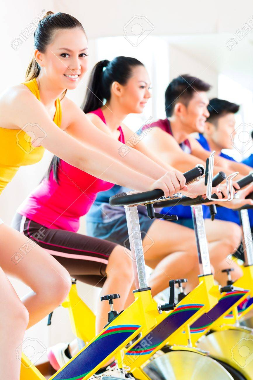 Chinese Asian sport group of men and women in fitness club or gym exercising on spinning bikes Stock Photo - 22880463