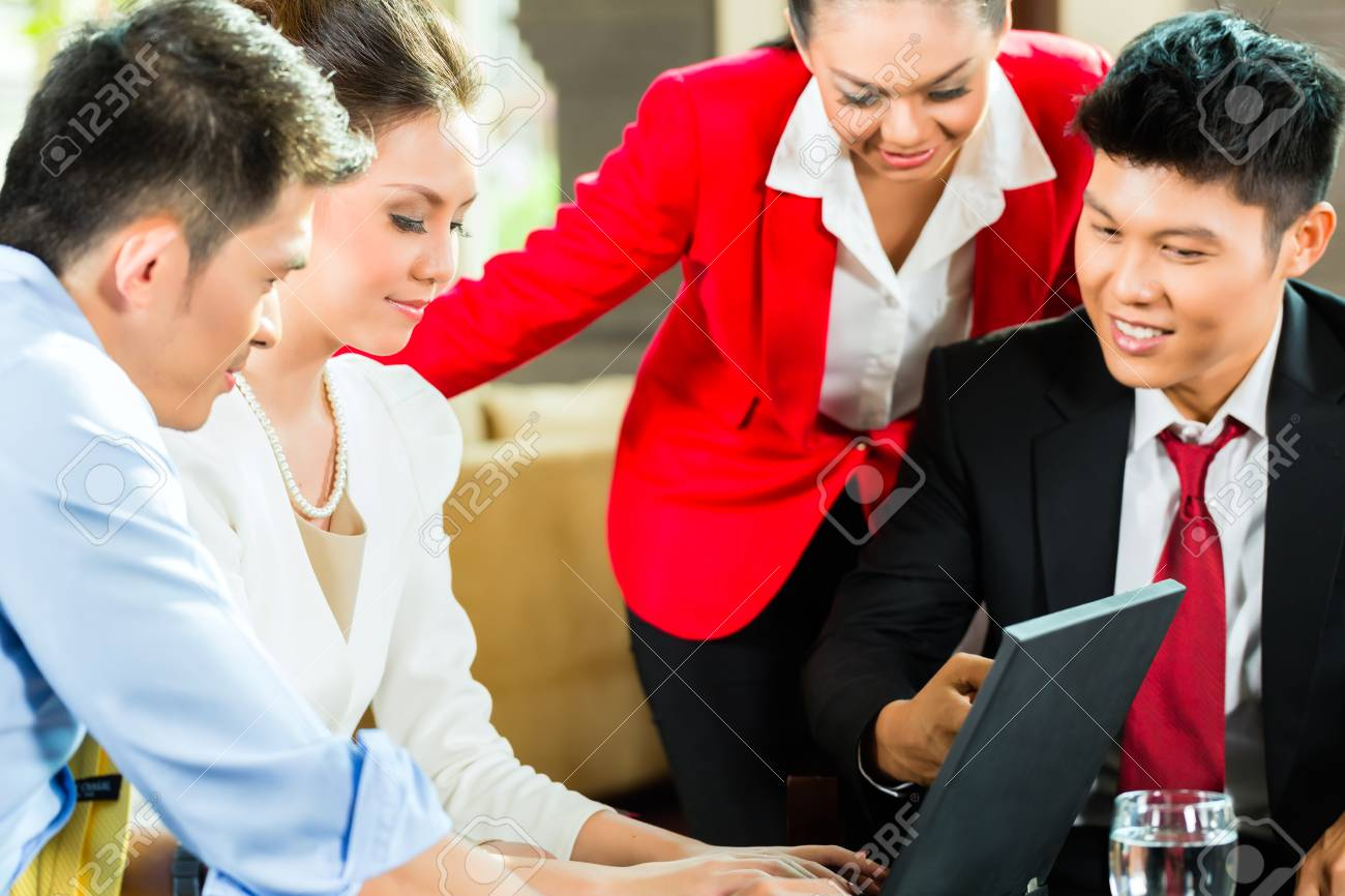 Four Chinese Asian business men and women having meeting in a hotel lobby looking at documents on laptop and drinking coffee Stock Photo - 23511572