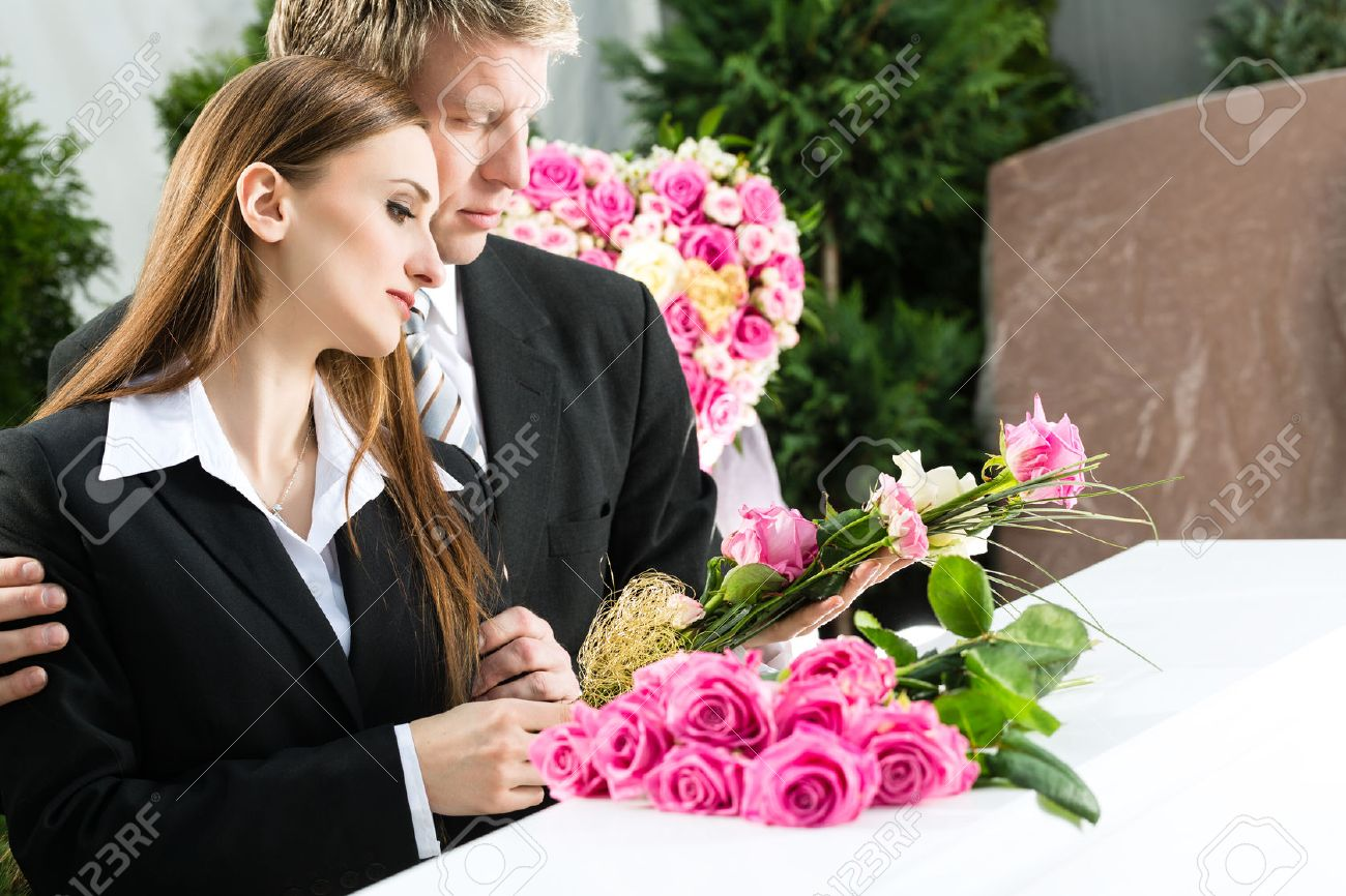 Mourning Man And Woman On Funeral With Pink Rose Standing At Stock