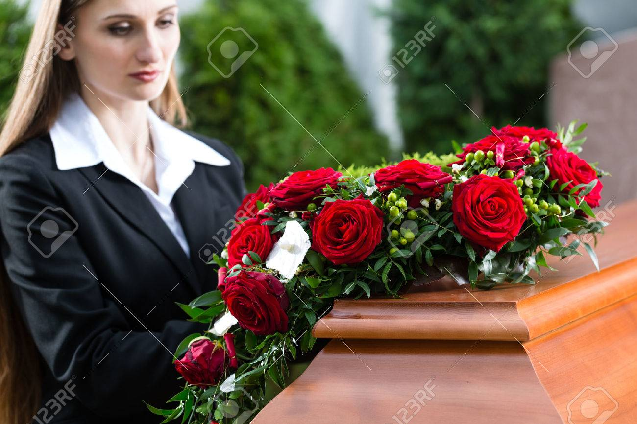 Mourning Woman On Funeral With Red Rose Standing At Casket Or