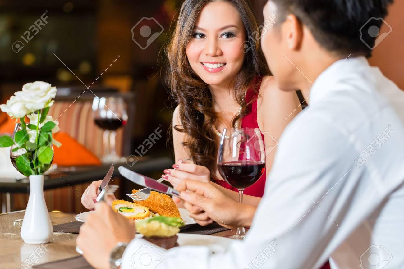 Asian Chinese couple - Man and woman - or lovers flirting and having a date or romantic dinner in a fancy restaurant Stock Photo - 25002035