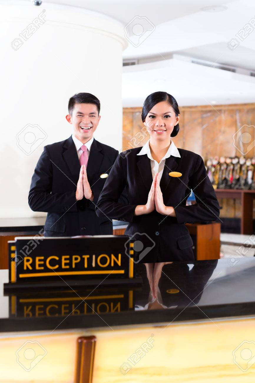 Chinese Asian reception team at luxury hotel front desk welcoming..