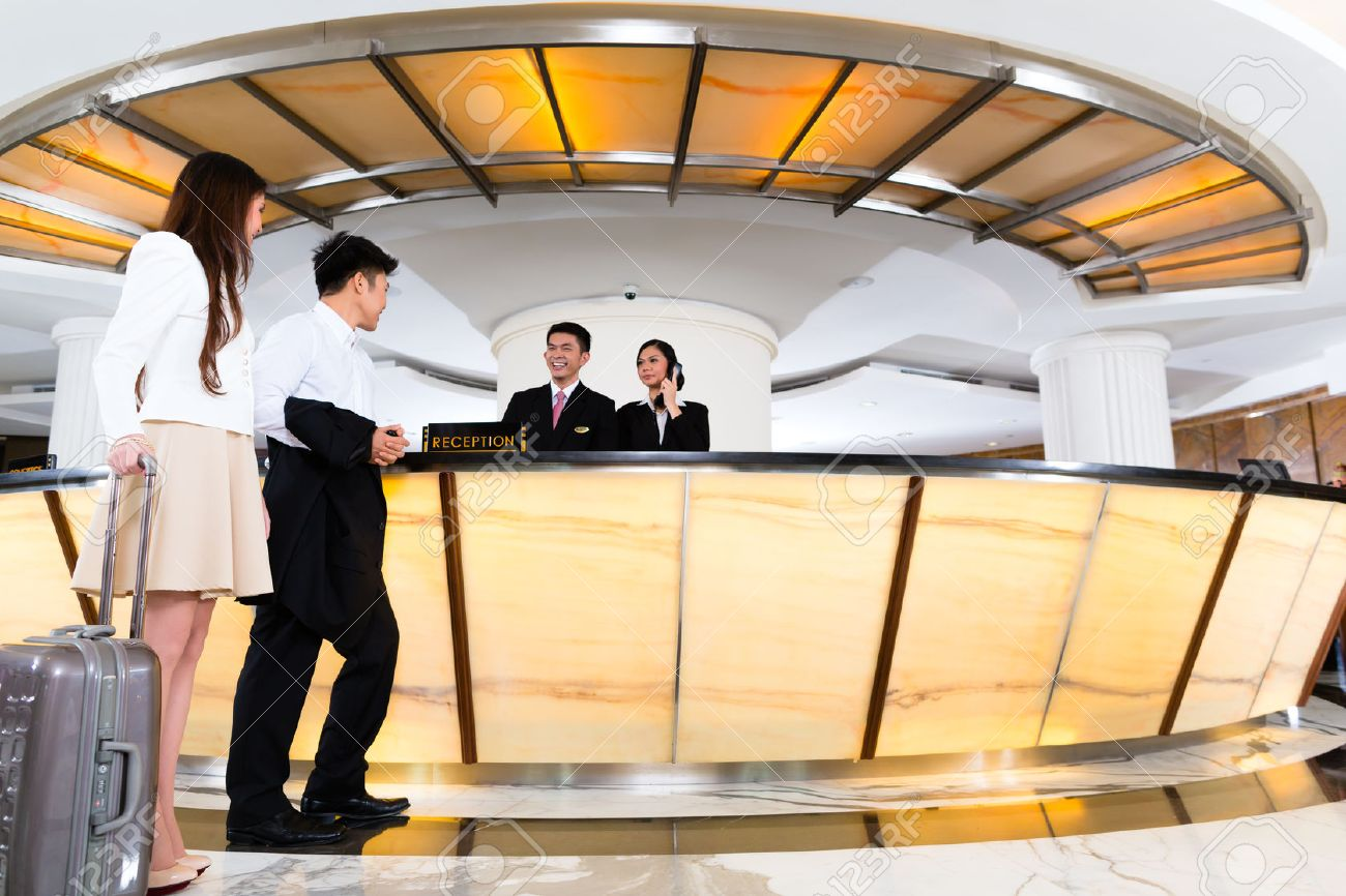Asian Chinese woman and man arriving at front desk or reception..