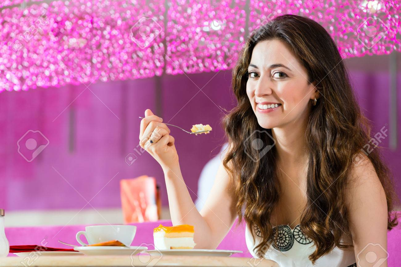 Young woman in a cafe or ice cream parlor eating a cake, maybe she is single or waiting for someone Stock Photo - 25003664