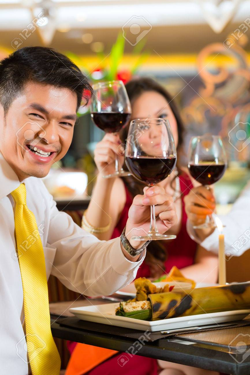 Two Asian Chinese Couples or friends or business people toasting during dinner or lunch in a elegant restaurant with red wine glasses Stock Photo - 25602571