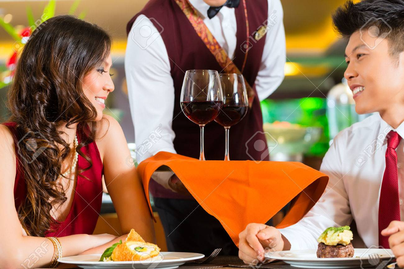 Asian Chinese waiter or steward serving man and woman or couple red wine in glasses on a tray in fancy restaurant or hotel Stock Photo - 25602813