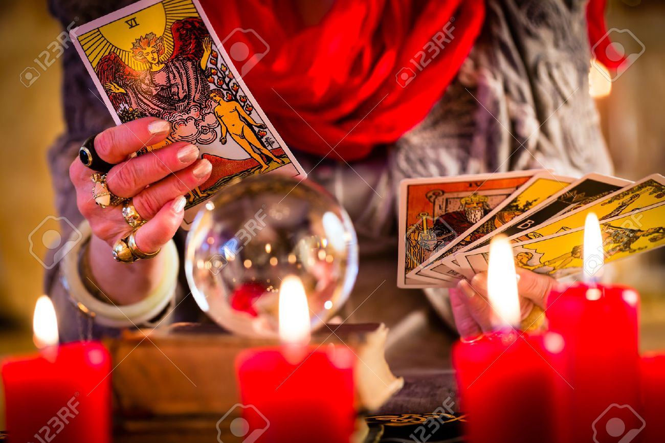 Female Fortuneteller or esoteric Oracle, sees in the future by playing her tarot cards during a Seance to interpret them and to answer questions - 25602986