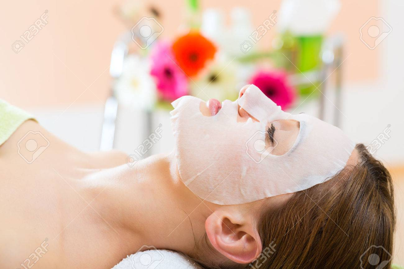 Wellness - woman receiving facial mask in spa for clean skin - 25774809