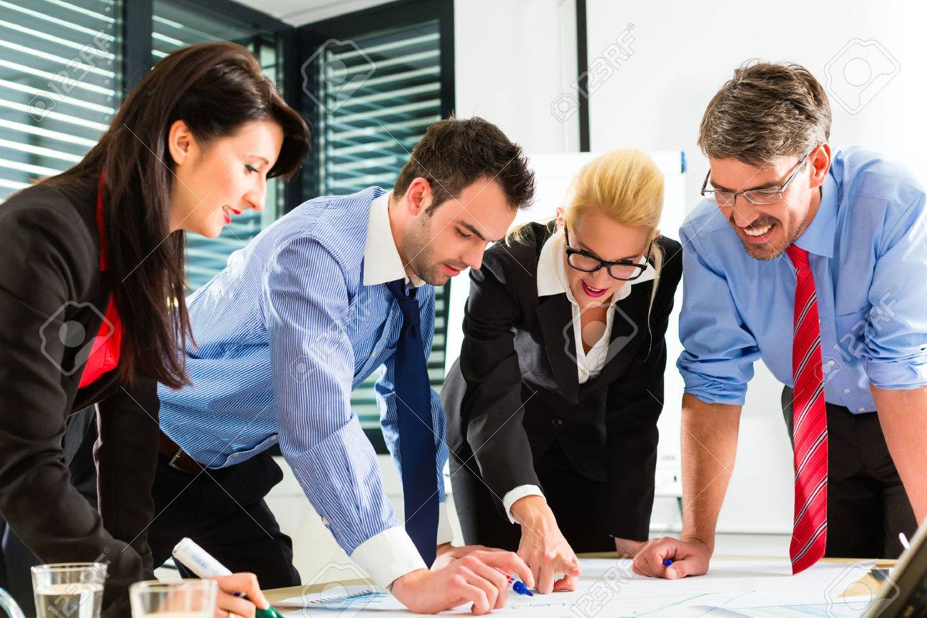Four professionals in the office in business clothes when planning a strategy for the future of the business Stock Photo - 26324931