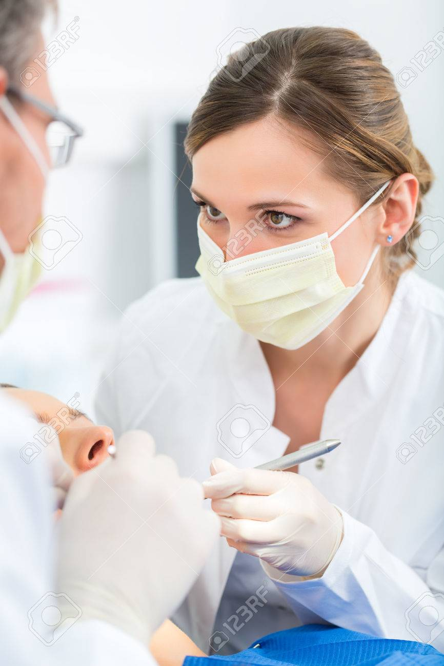 Female patient with dentist and assistant in a dental treatment, wearing masks and gloves Stock Photo - 26449927