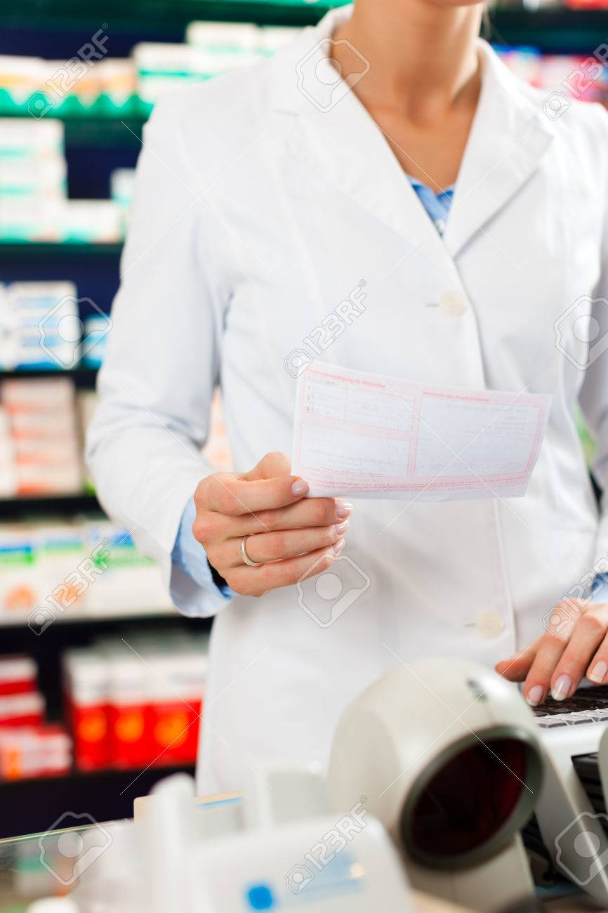 Female Pharmacist In Pharmacy Standing At The Cashier She Is