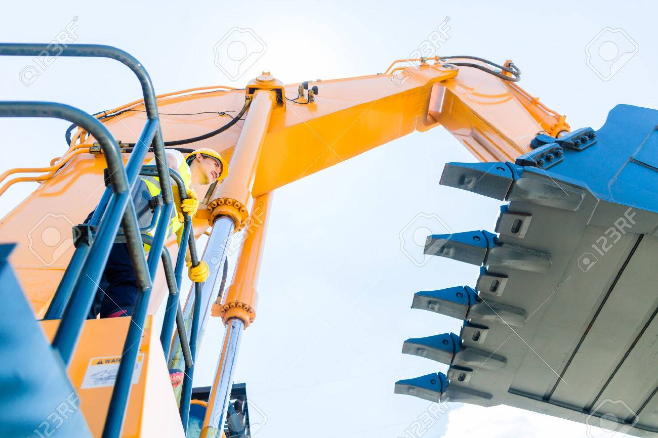 Asian driver standing on construction machinery on building site Stock  Photo - 29284892