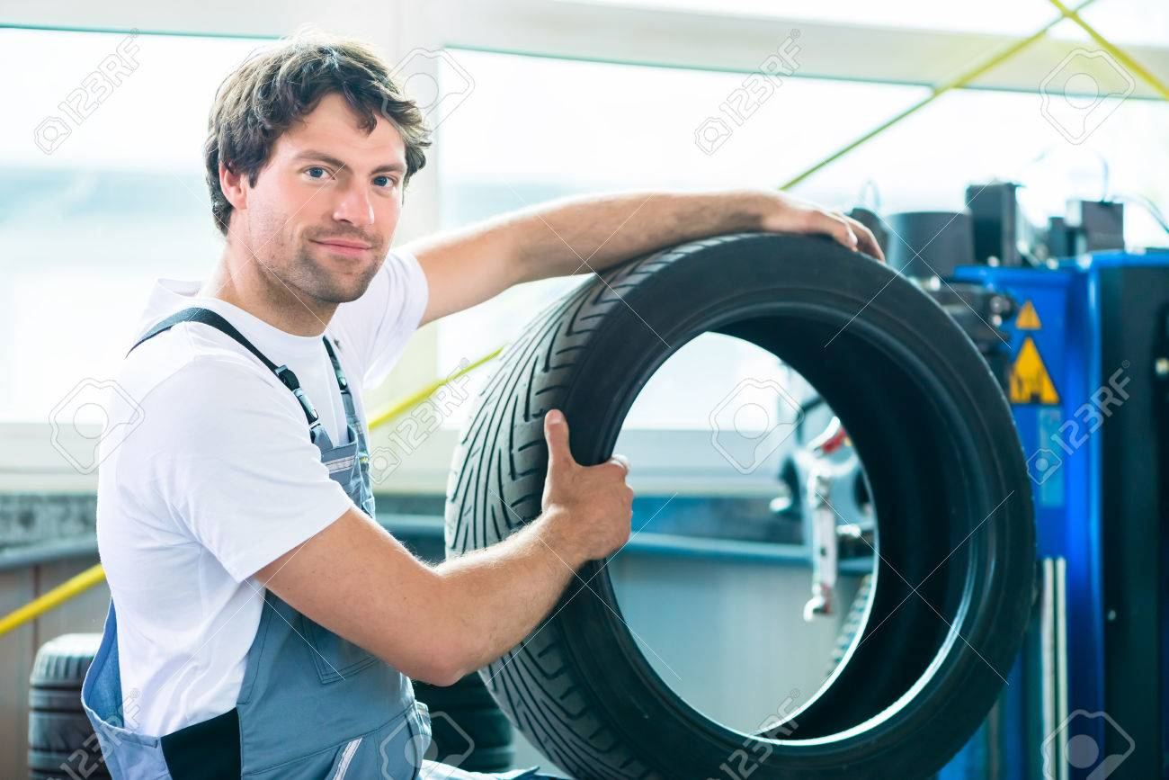 auto mechanic changing tire in car workshop stock photo picture auto mechanic changing tire in car workshop stock photo 32044357