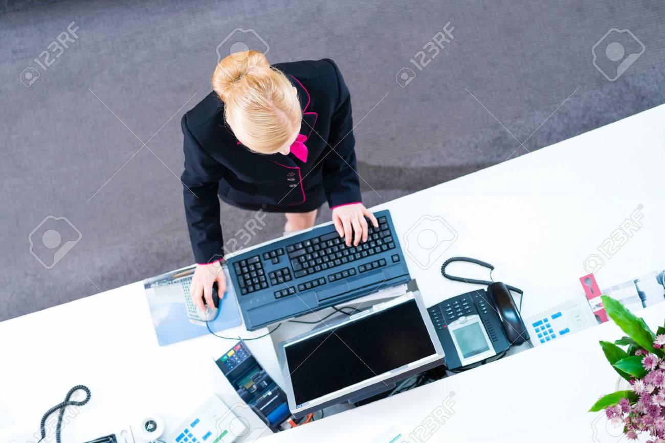 Hôtel réceptionniste travaillant sur ordinateur au bureau de la