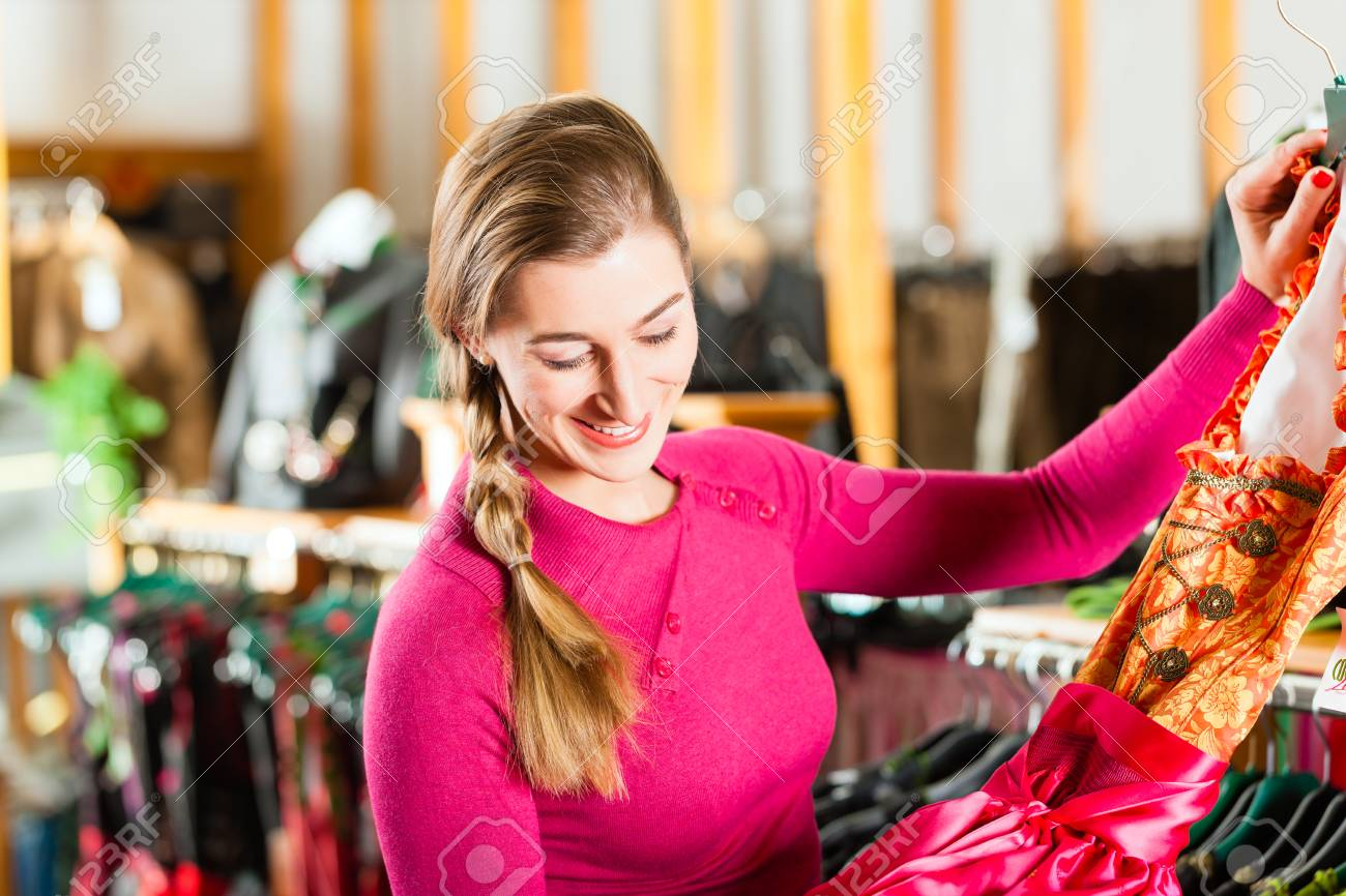 a6c04c92f35 Stock Photo - Traditional clothes -young woman is buying Tracht or dirndl  in a shop