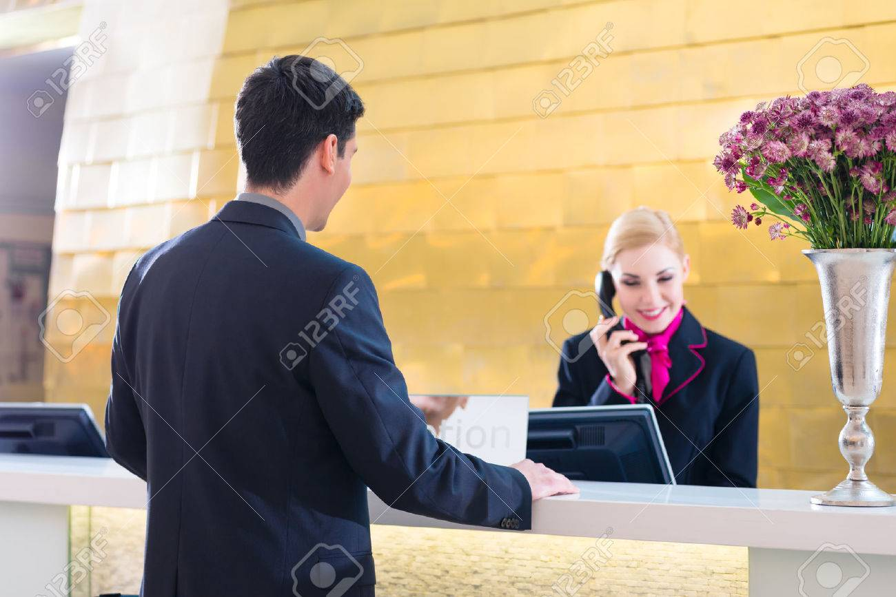 Hotel receptionist telephoning with guest for reservation or information - 33725031