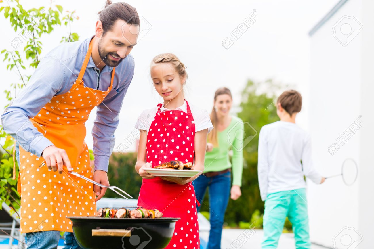 Father And Daughter Barbecue Meat Spits And Sausages At Family ...