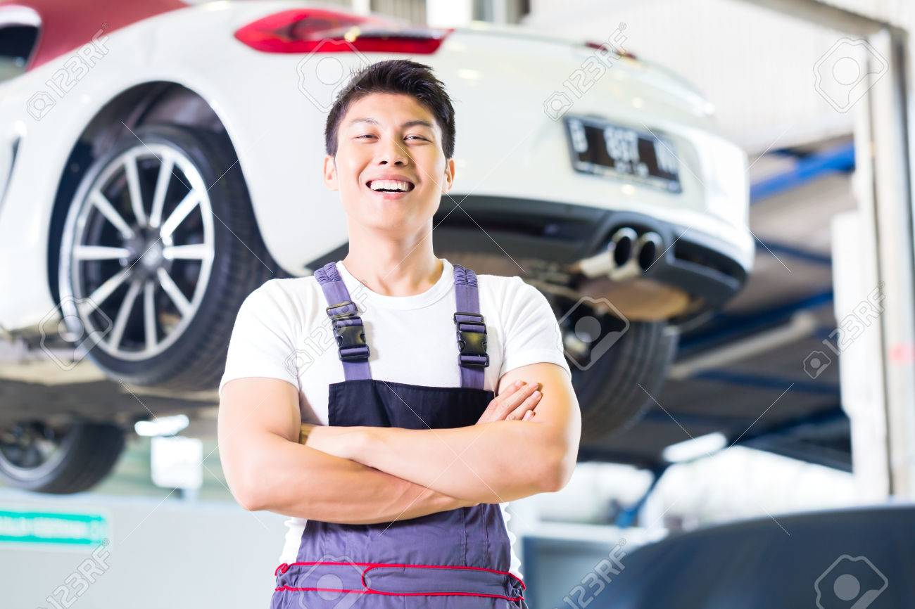 Asian Chinese Car Mechanic Standing In Front Of Luxury Car In
