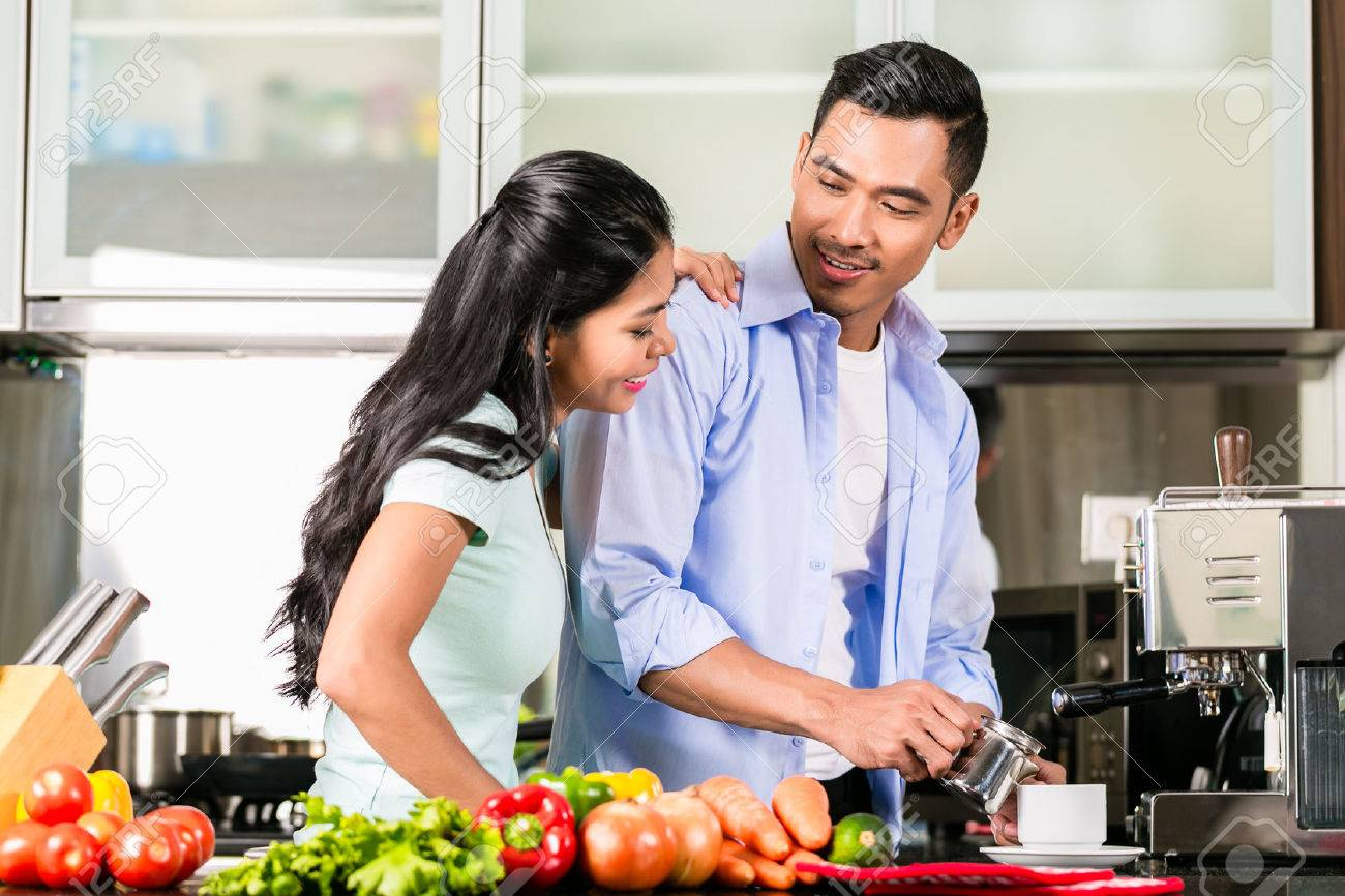 Asian couple, man and woman, cooking food together in kitchen and making coffee - 37791200