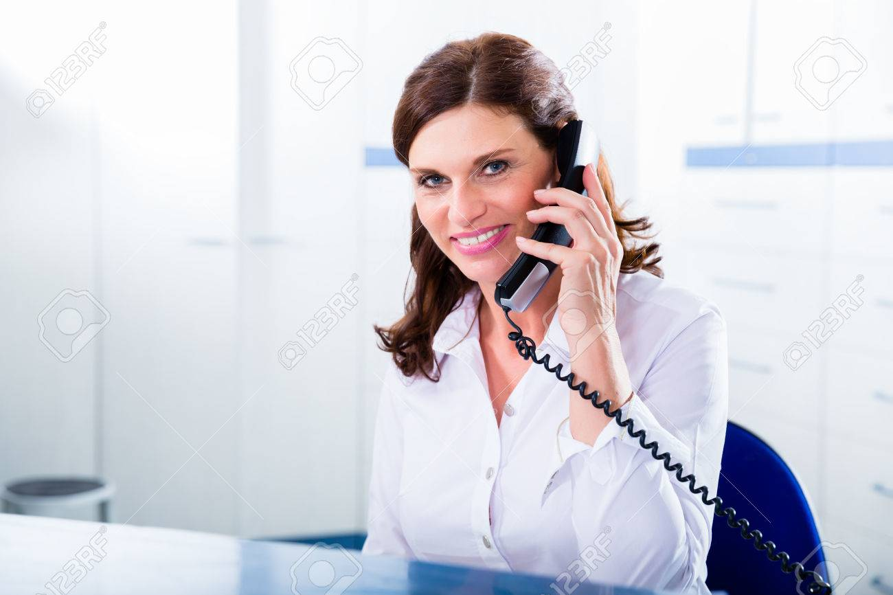 Doctors nurse with telephone in front desk making appointment with patient - 37802096