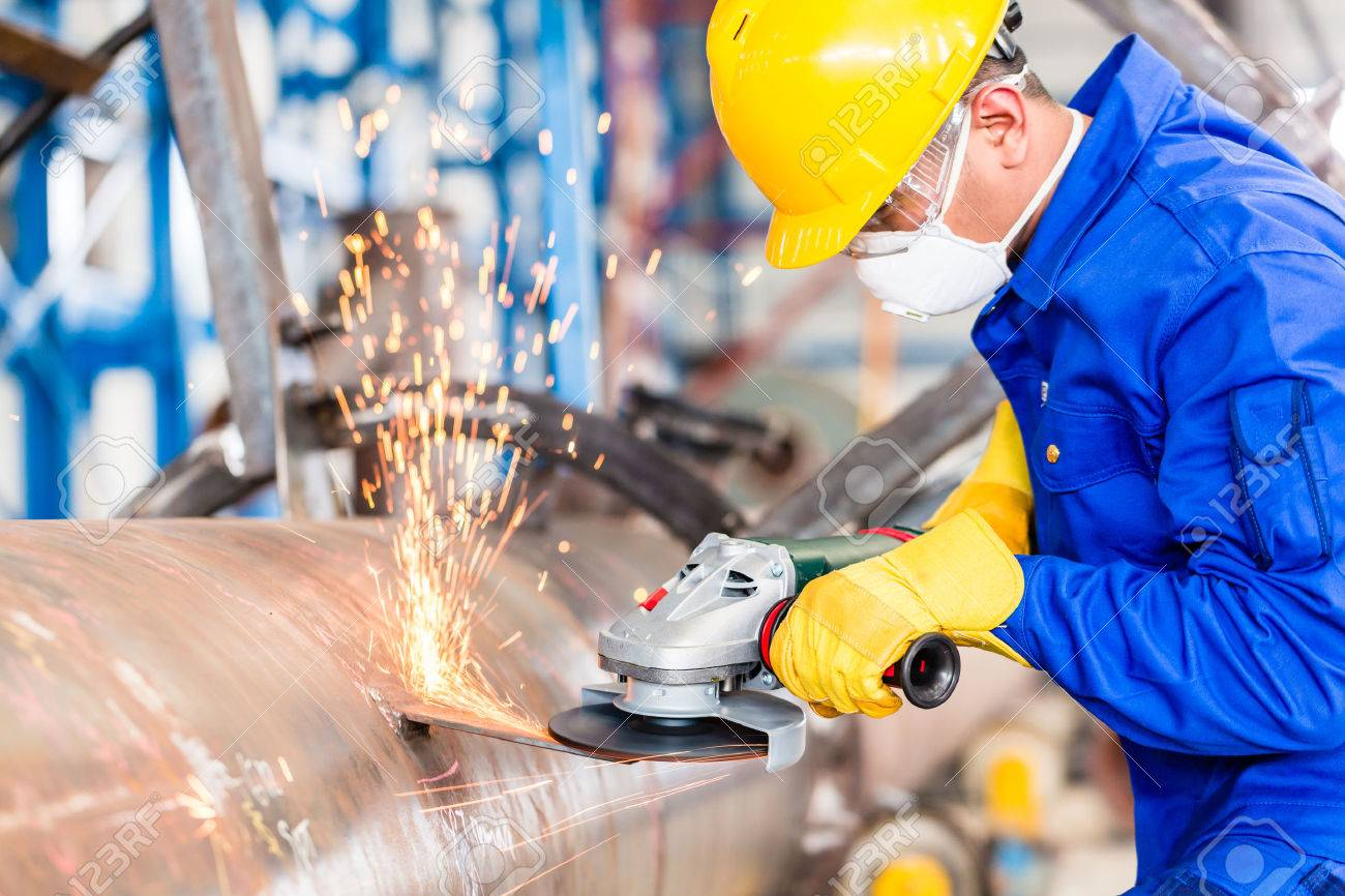 Industrial worker in manufacturing plant grinding to finish a pipeline - 37847132