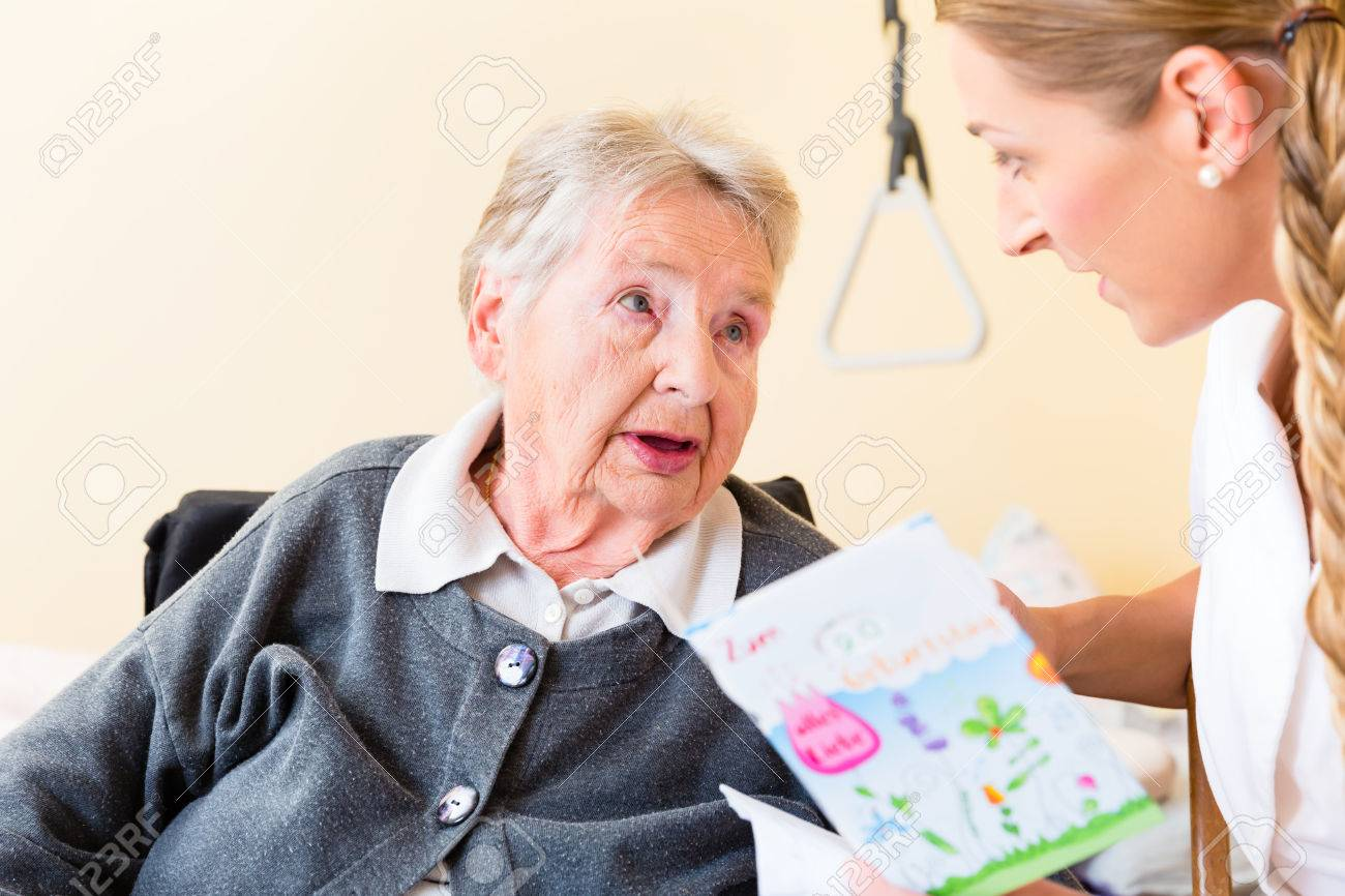 Nurse giving birthday card to senior woman in nursing home sitting nurse giving birthday card to senior woman in nursing home sitting in wheelchair stock photo bookmarktalkfo Images