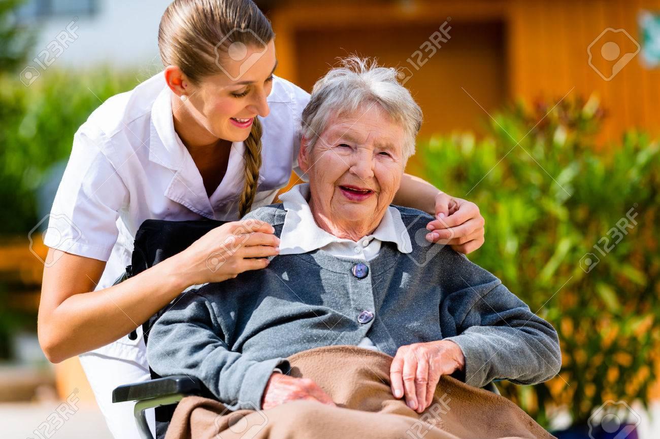 Senior woman in nursing home with nurse in garden sitting in wheelchair - 37893895