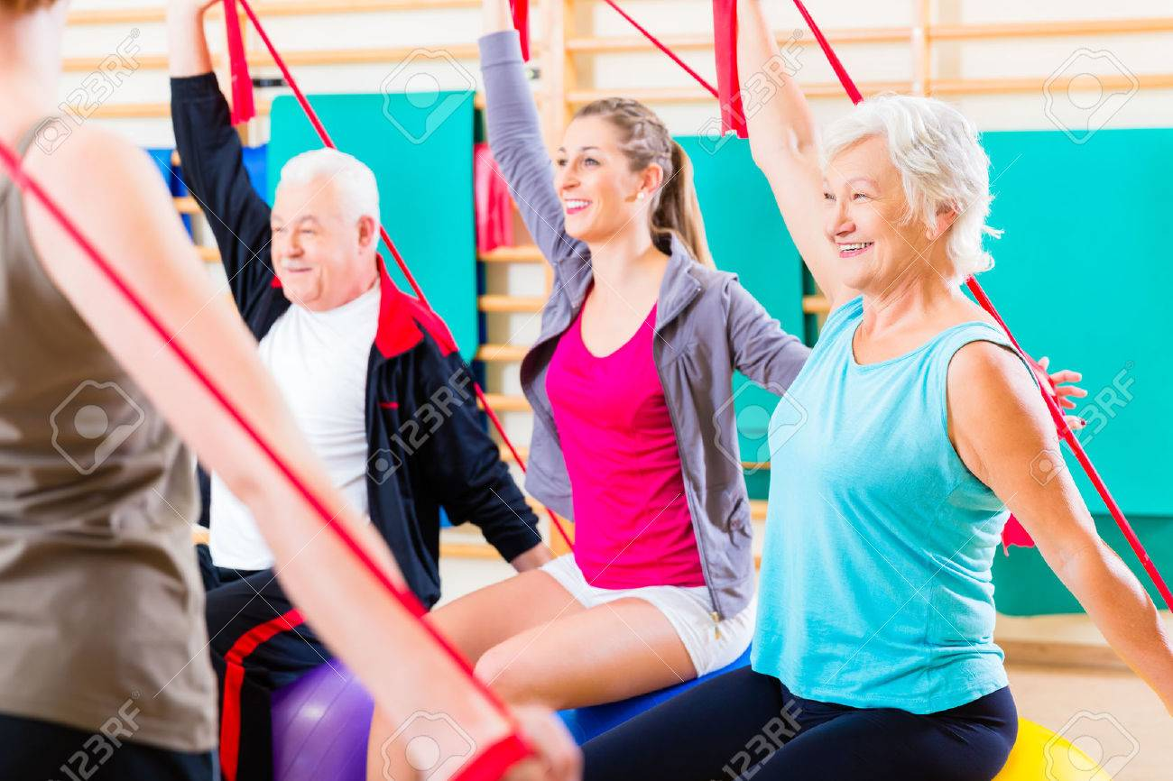 Senior people at fitness course in gym exercising with stretch band - 37922685