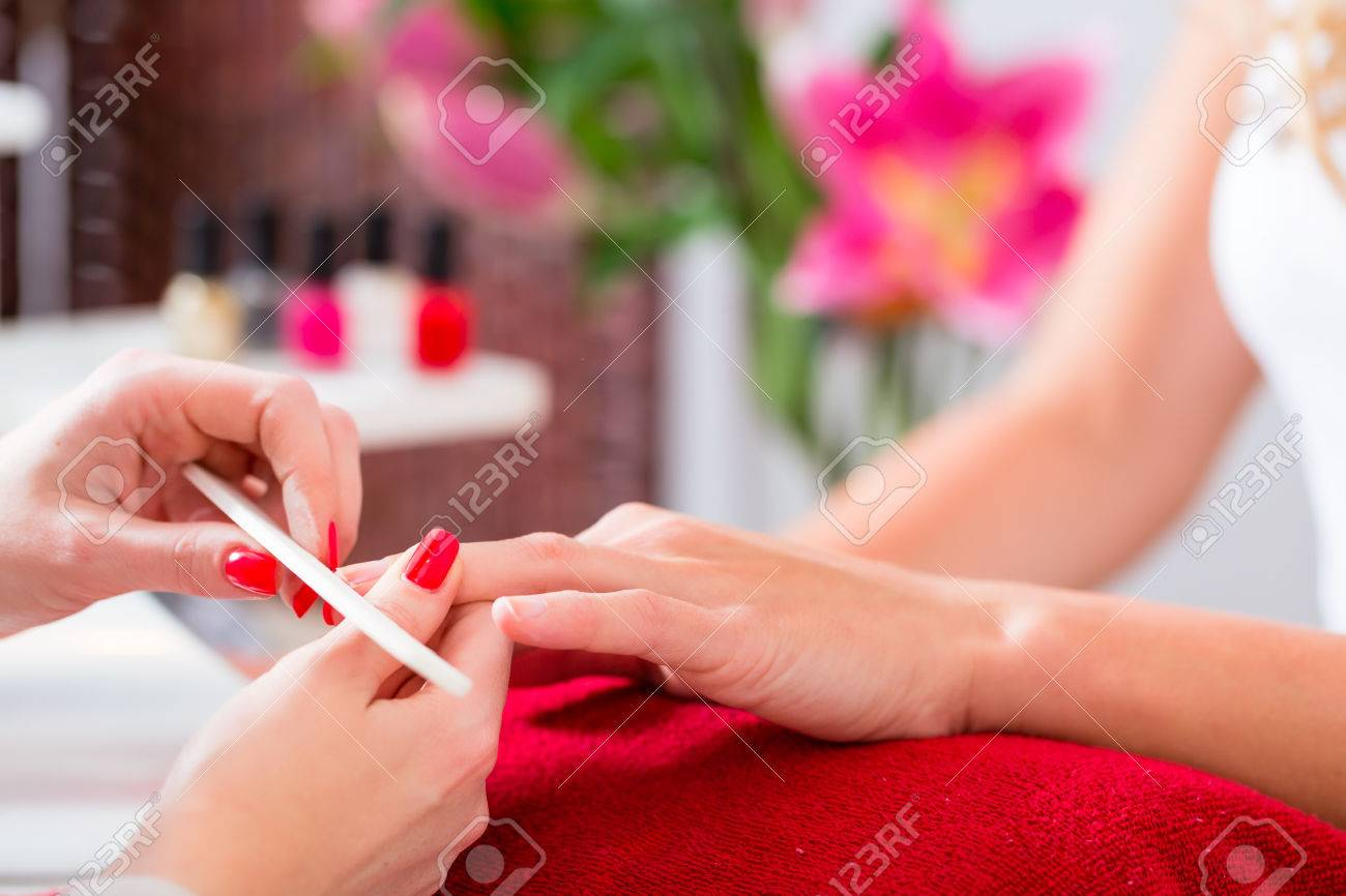 Woman Getting Manicure In Nail Parlor With File, Close Shot Stock ...