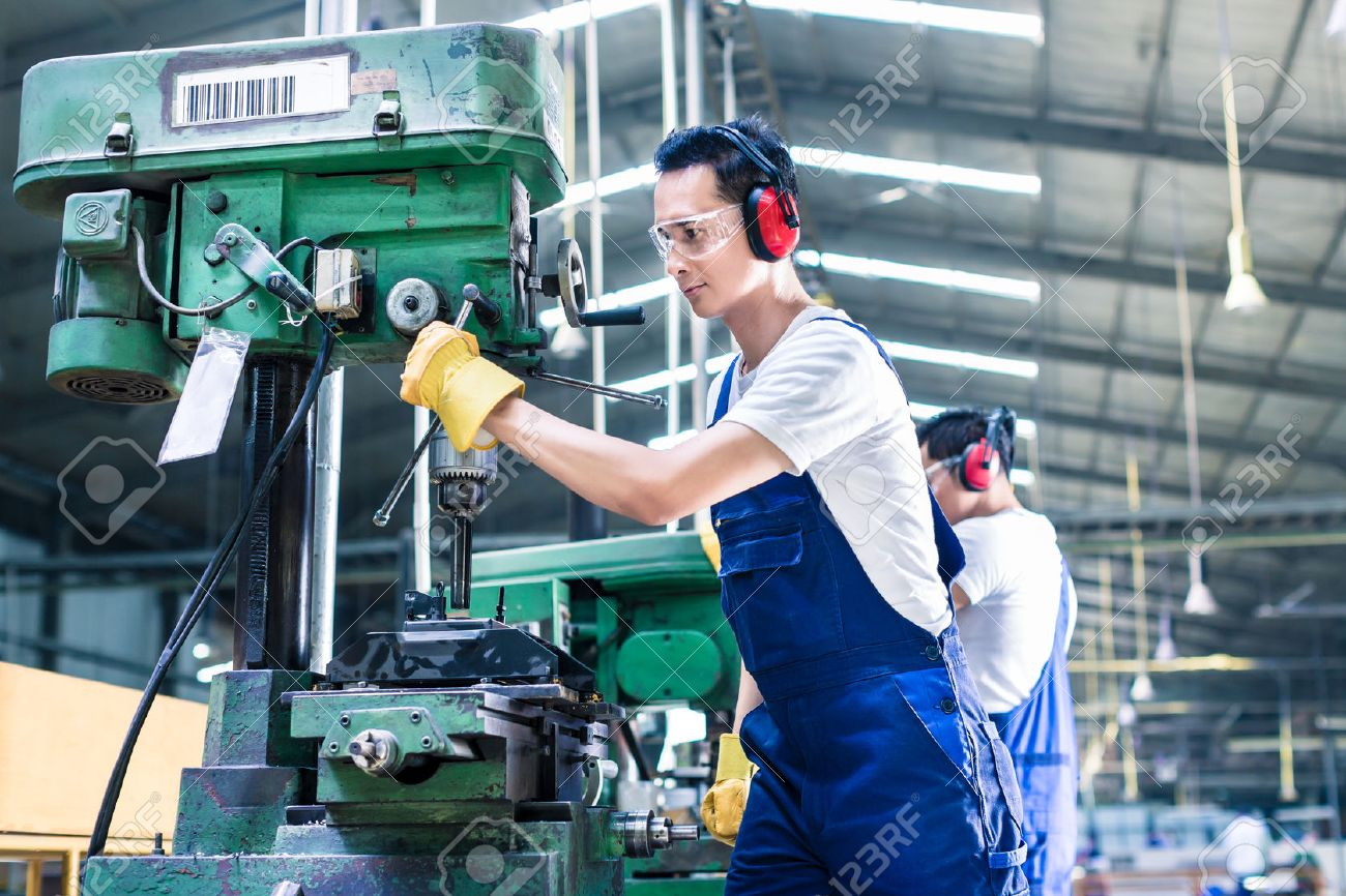 Asian Worker In Production Plant Drilling At Machine On The Factory Floor Stock Photo