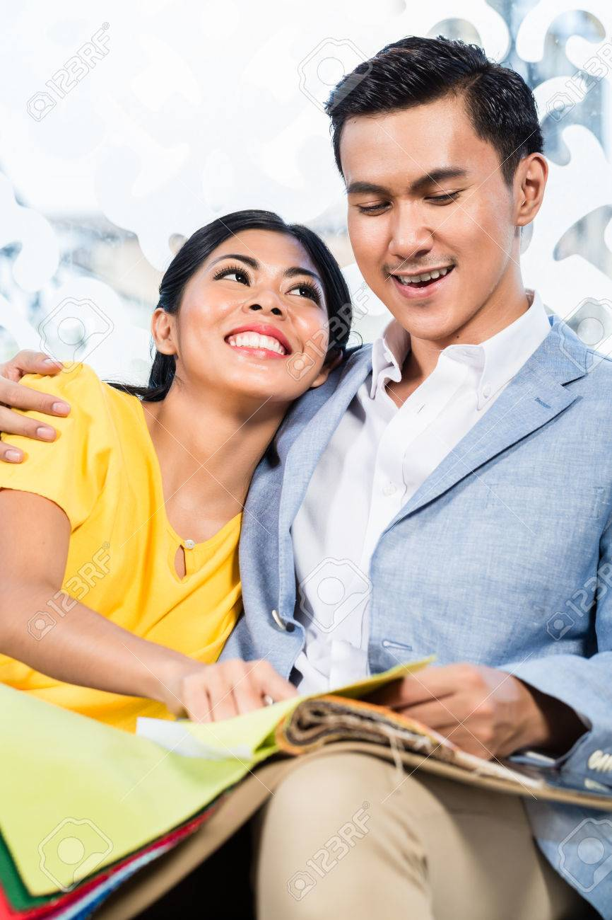 asian couple buying sofa in furniture store, sitting on couch