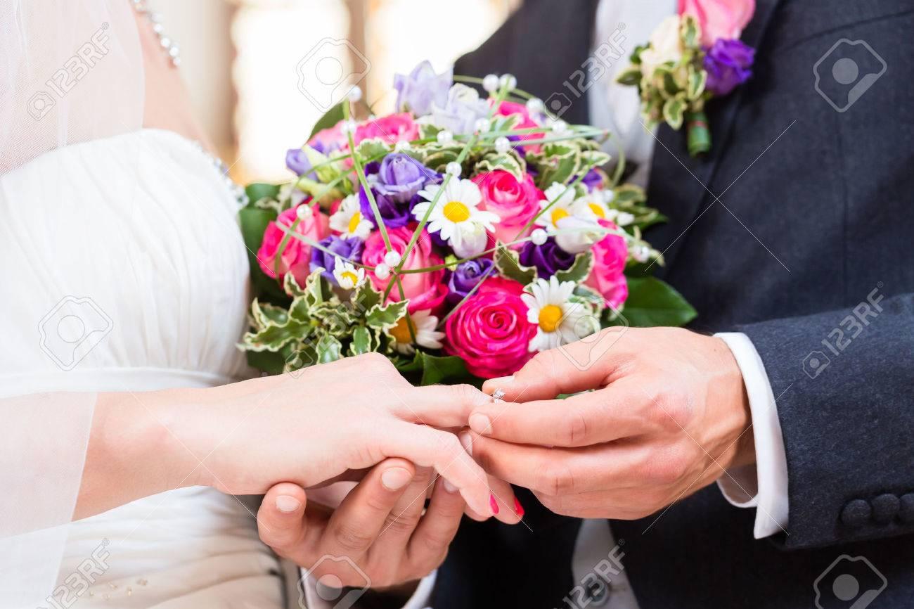 Groom slipping ring on finger of bride at wedding - 46812246