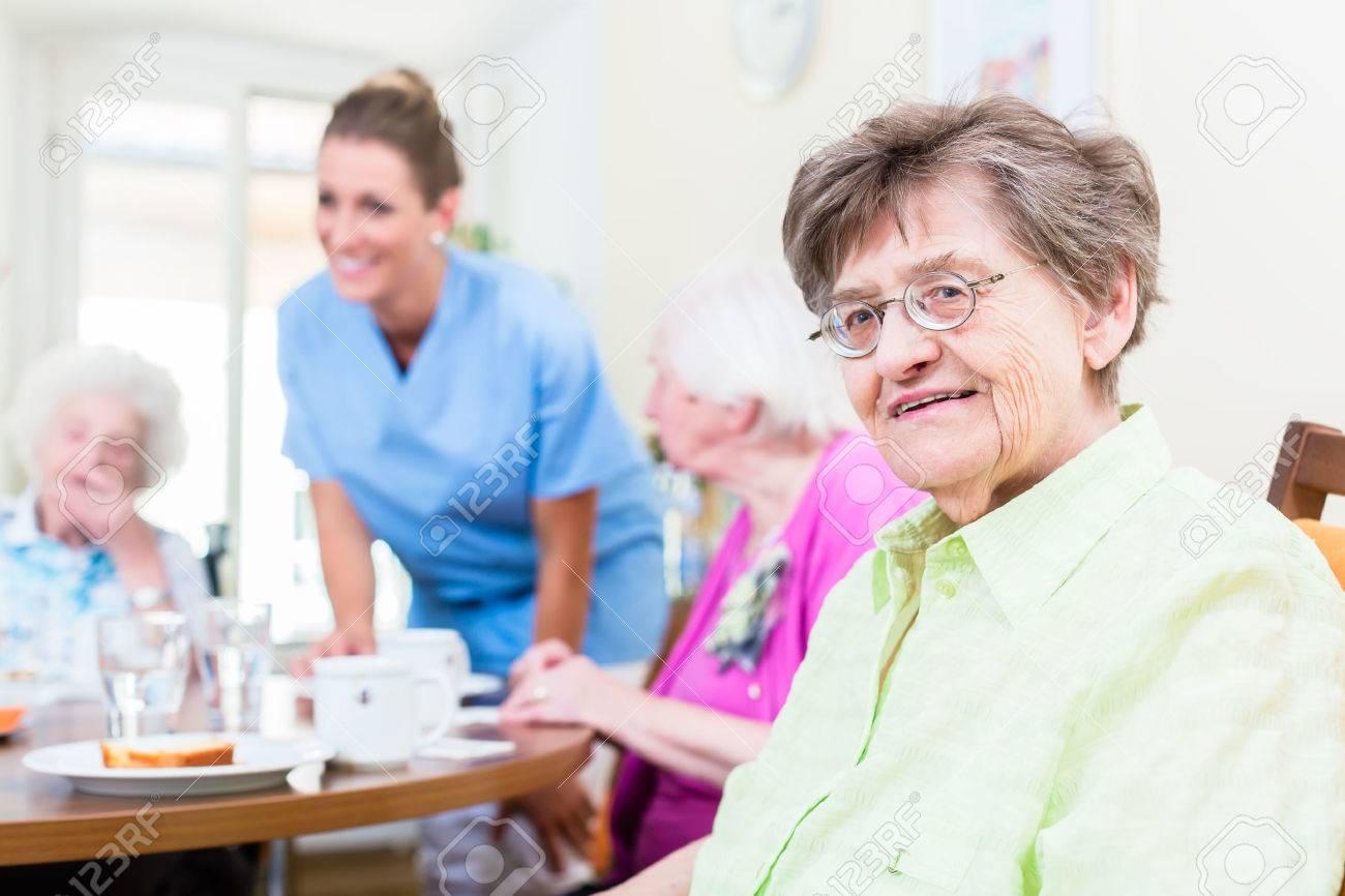 Group of seniors having food in nursing home, a nurse is serving Standard-Bild - 47847030